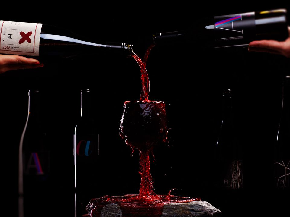 Bottles of red Moorilla wine being poured into an overflowing glass.