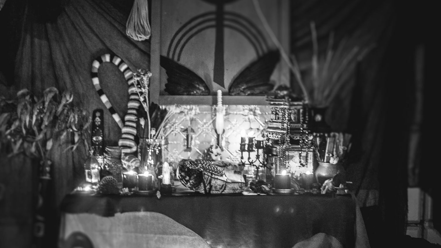 A slightly blurred image of a shrine with candles, flowers in vases and other oddities.