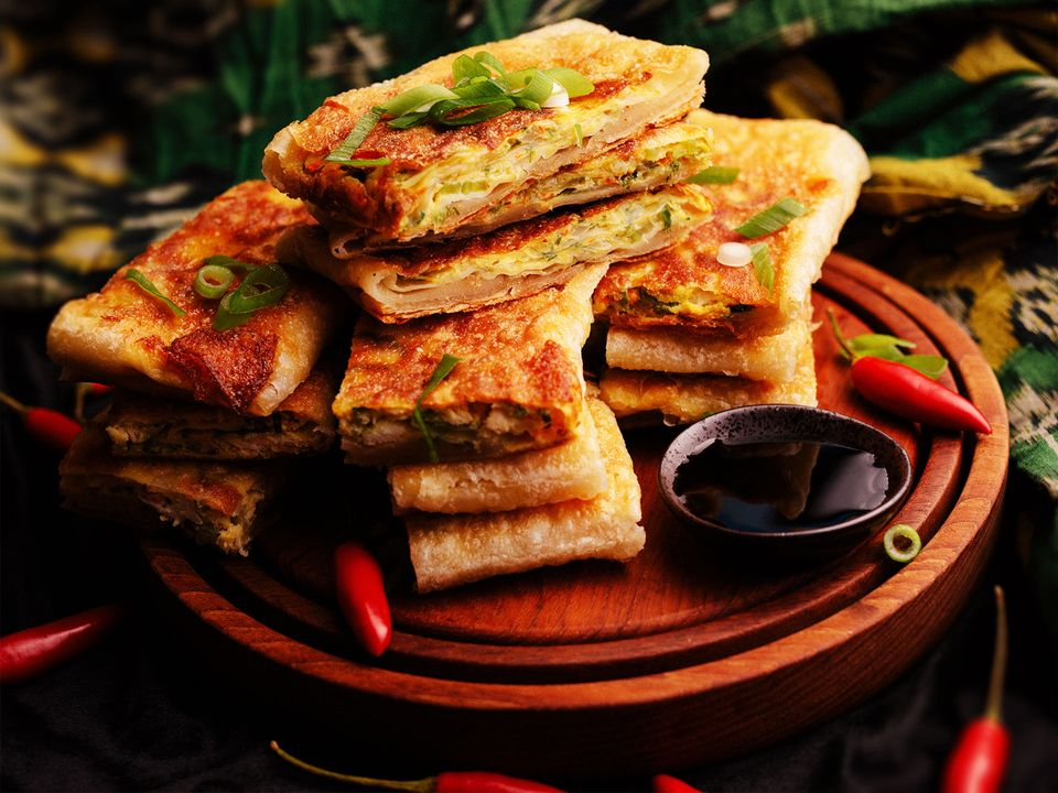 A stack of fried Indonesian pancakes topped with spring onion.