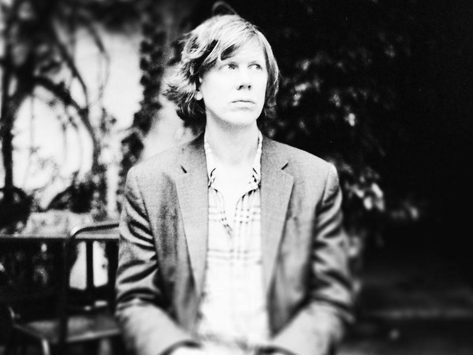 Thurston Moore sitting down, wearing a suit jacket and a button-down shirt, looking to the right.