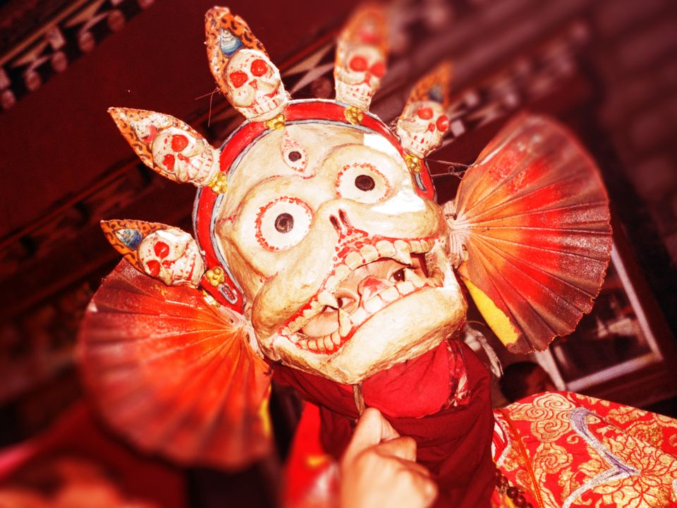 A person wearing a Tibetan skull mask.