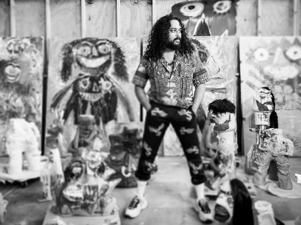 Artist Ramesh Mario Nithiyendran standing amongst a selection of his sculptures and paintings.