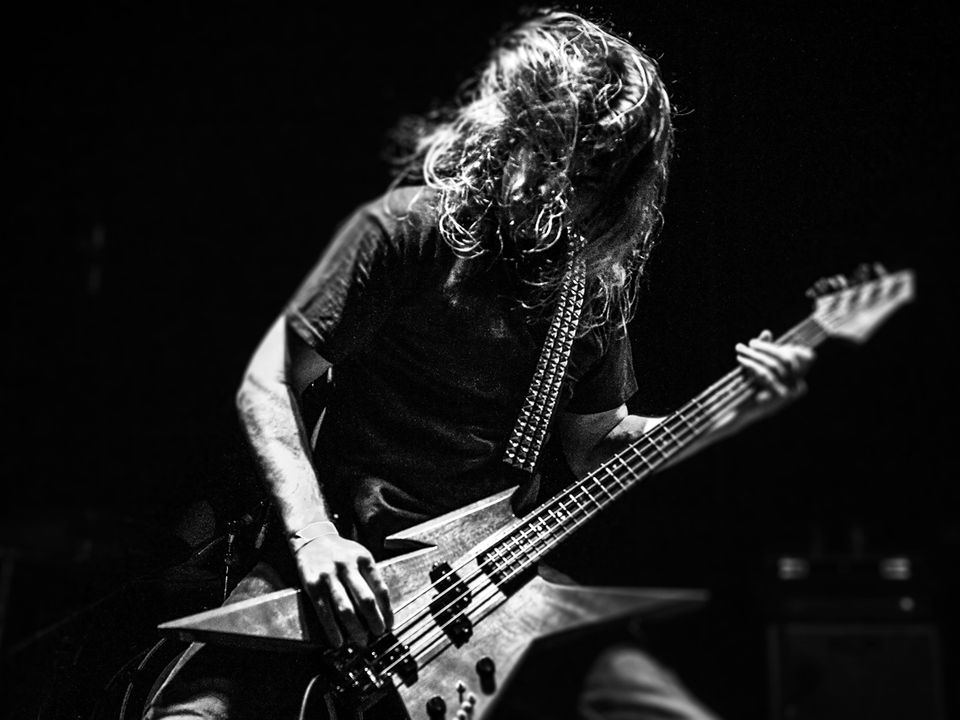 A musician from Misery plays the bass guitar.