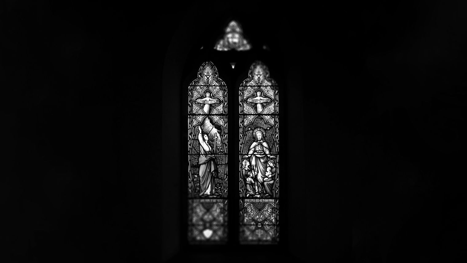 A stained glass window lit from behind, surrounded by darkness.