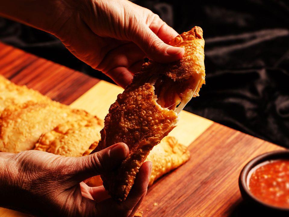 A pair of hands breaking open a hand-made, vegetarian empanada.