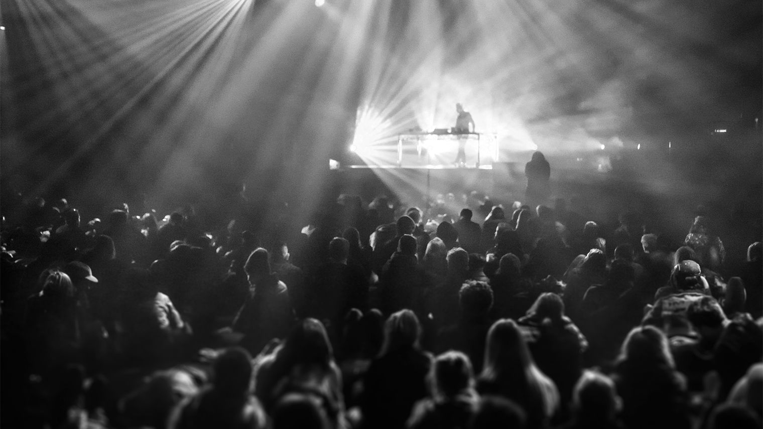 A large crowd surrounds a silhouetted figure on stage.