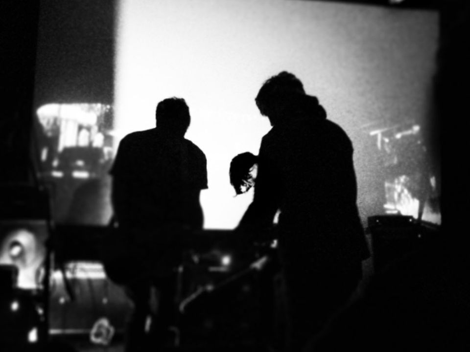 Three silhouetted figures focus on their instruments on stage.