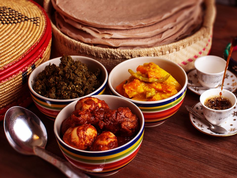 Ethiopian fare sitting in bowls alongside zesty fermented injera flatbread.