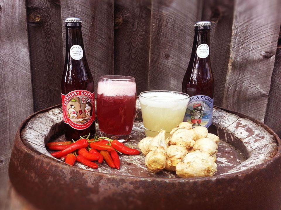Two bottles of Tasmanian Chilli Co. beer, surrounded by fresh chillies and ginger.