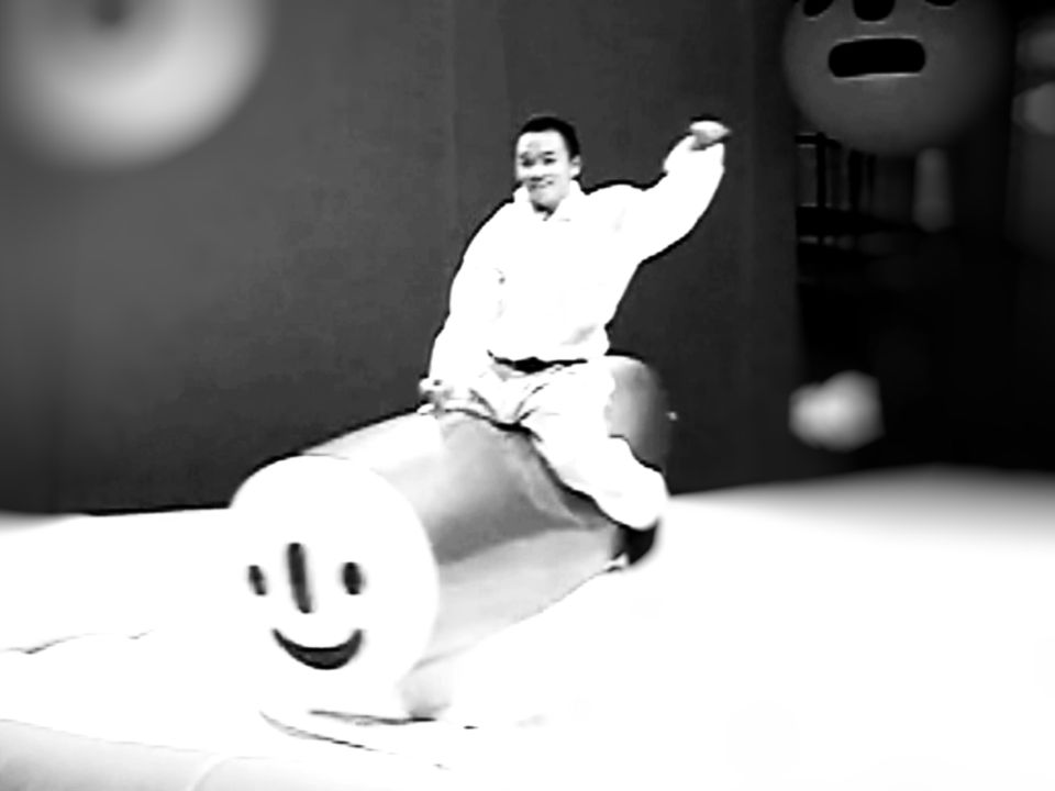 A person riding a smiley-faced mechanical bull.