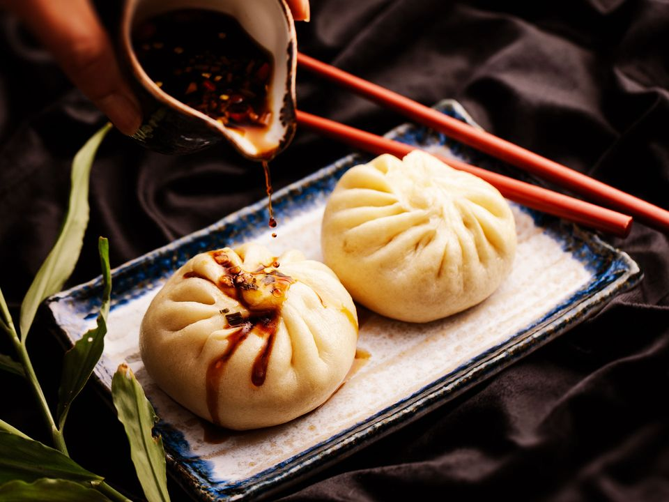 A hand pouring chilli oil onto two steamed pork buns, or Bao Zi.