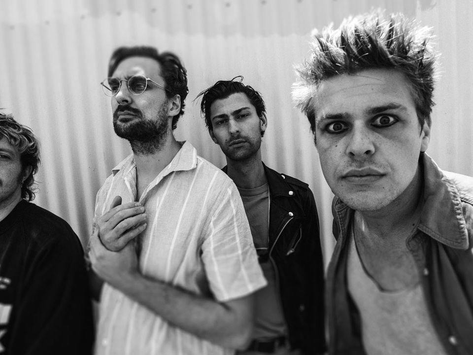 A person, with quite spiky hair, stares into your soul as their bandmates stand nonchalantly behind.