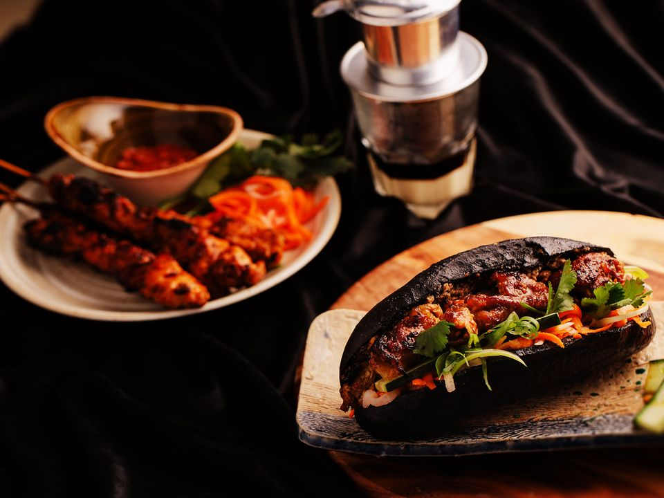A black banh mi loaded with pork and fresh vegetables.