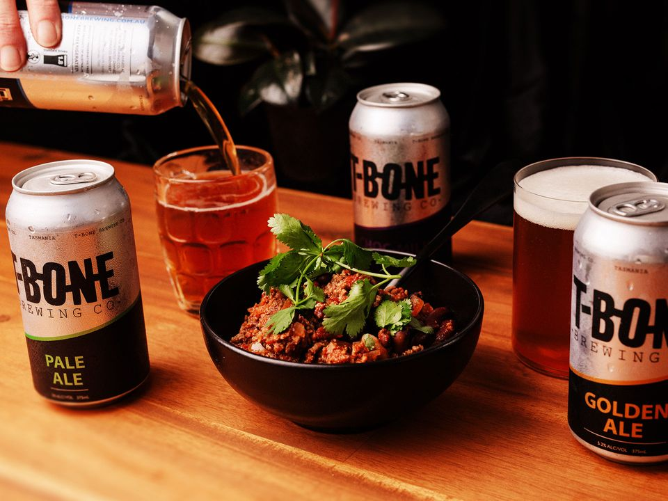 Cans of T-Bone Brewing Co. Pale Ale and Golden Ale, alongside a bowl of prime Tasmanian beef and bean chilli topped with parsley.