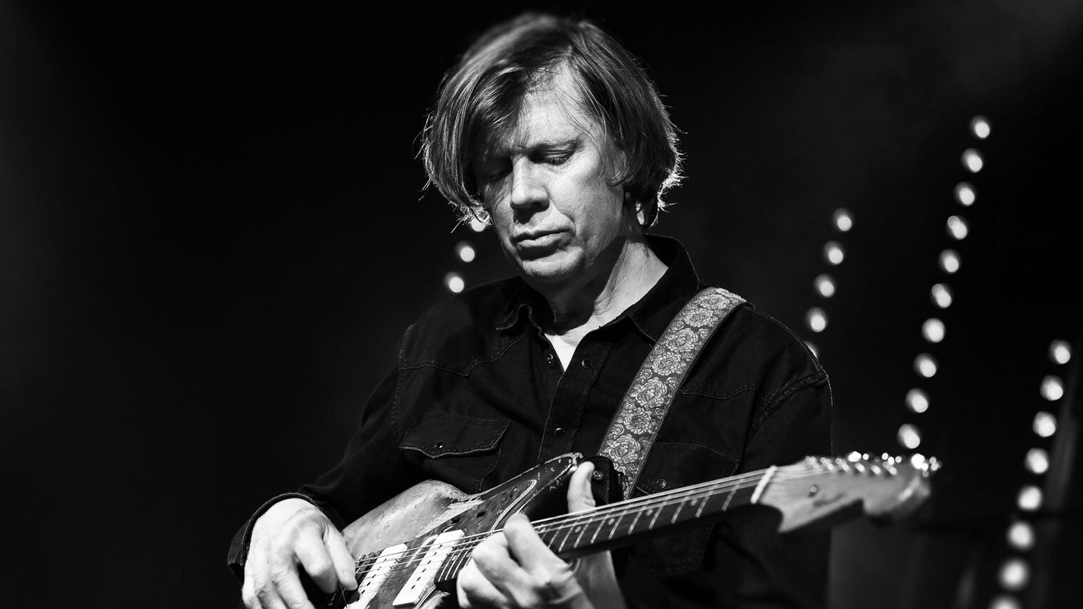 Thurston Moore, seated, playing guitar.