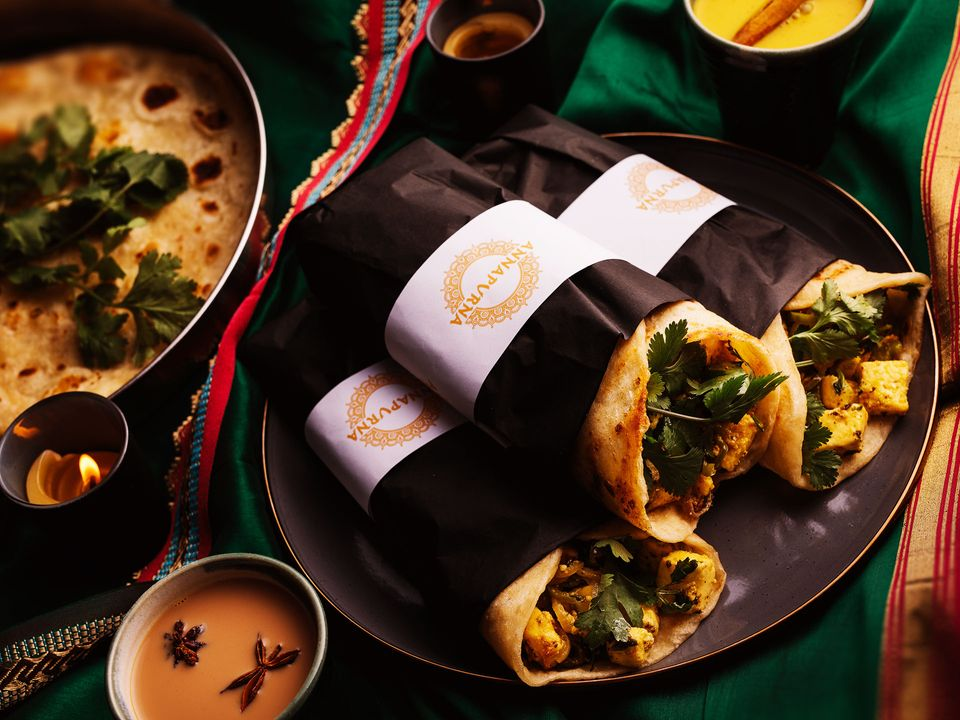 Three vegetarian kathi rolls served with naan.