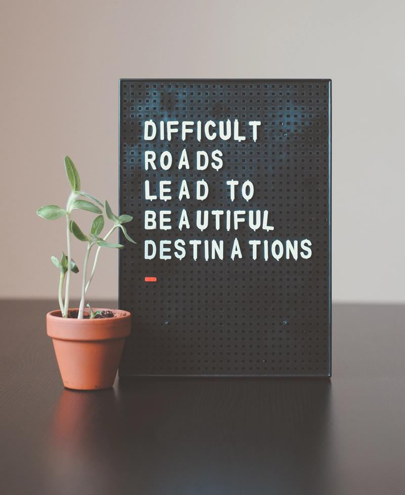 Picture of a board that reads difficult roads lead to beautiful destinations.