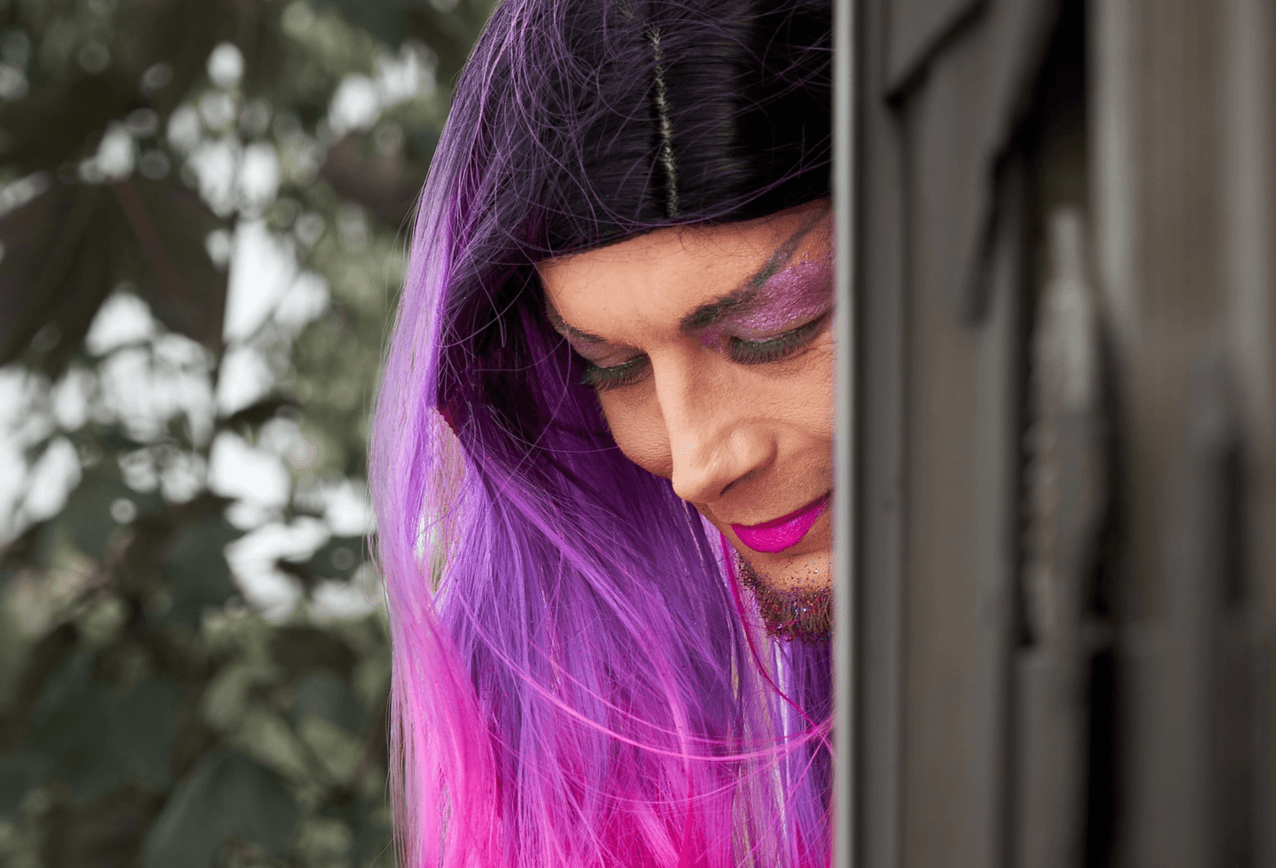 Drag queen with purple hair looking down
