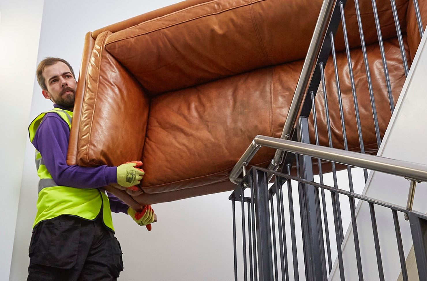Waste operative carying a sofa downstairs