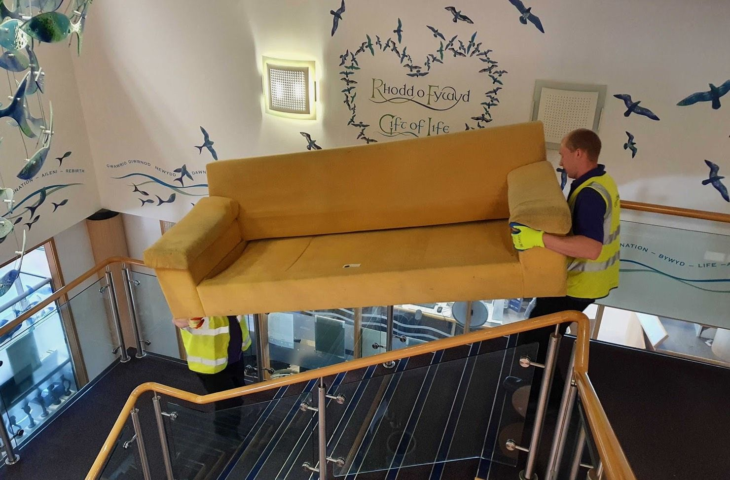 operatives carrying sofa downstairs