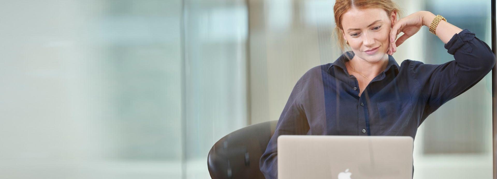 Kvinne sitter foran datamaskin