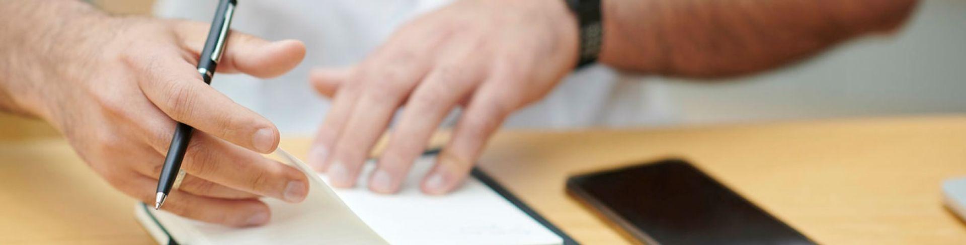 Arbeidsmøte med penn og mobiltelefon i forgrunnen