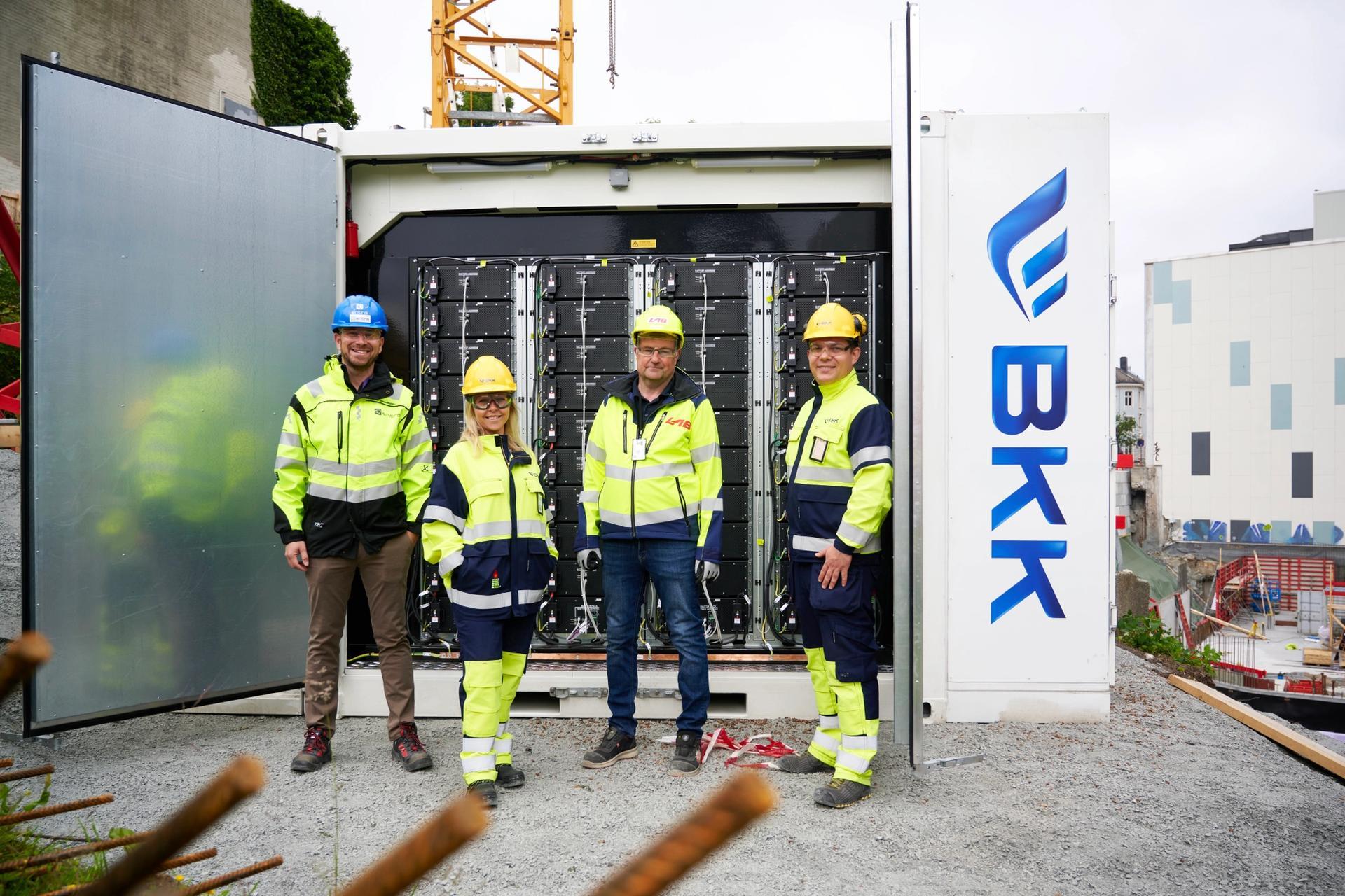 Dette 11 tonn tunge batteriet skal blant annet gi strøm til en tårnkran og byggtørking. F.v. Sturla Hjelmervik (Entra), Camilla Moster (BKK), Inge Andersen (LAB Entreprenør) og Kjetil Strand Solheim (BKK). Foto: Helge Hansen / BKK.
