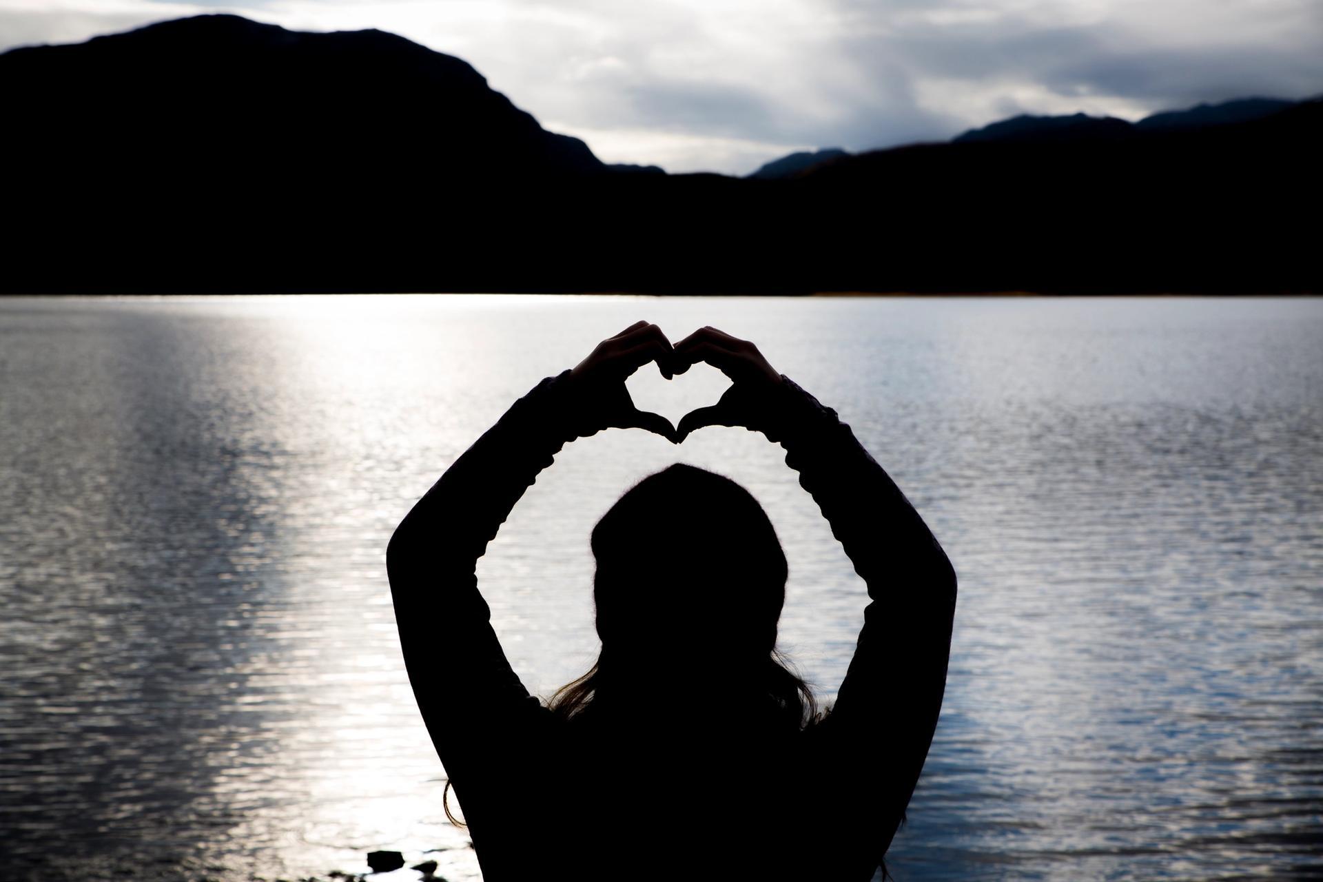 Silhuett av kvinne foran innsjø