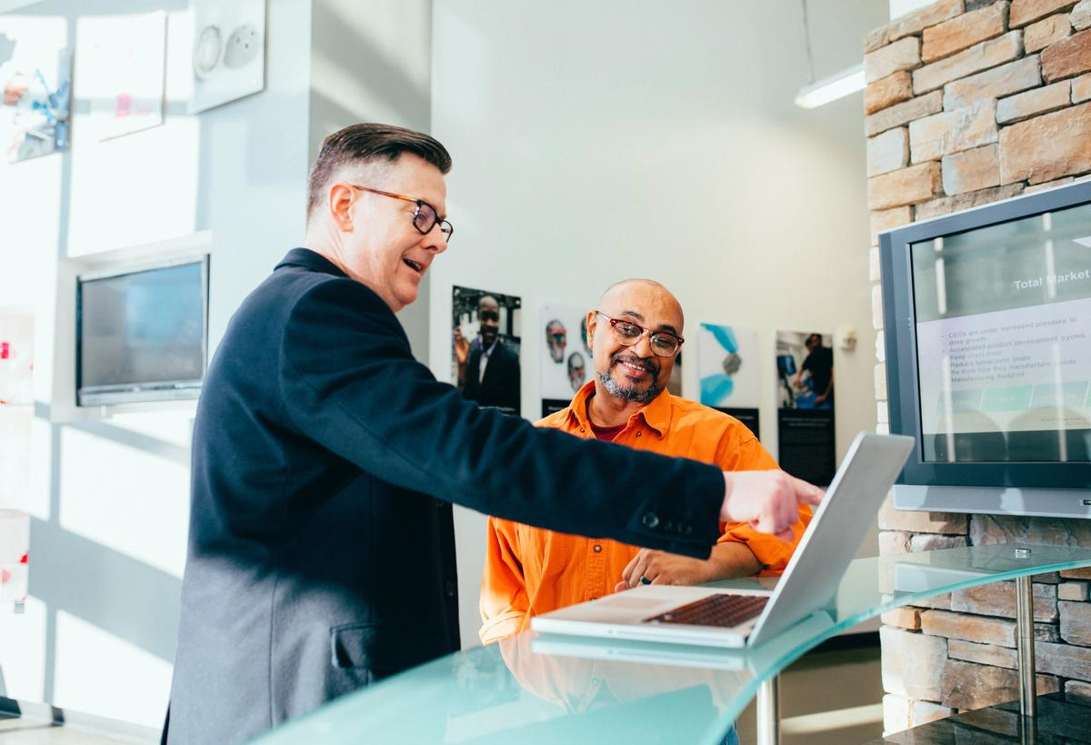 A salesman and business owner looking at data on a laptop