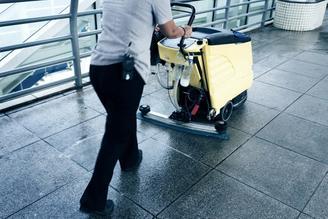 Siivoaja siivoaa lattioita koneella