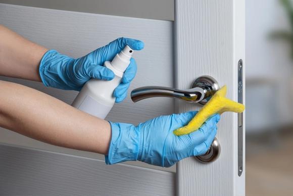 Kotisiivous käynnissä. jossa siivoaja pesee ovenkahvaa.