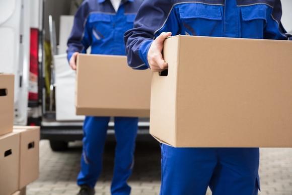 Muuttomiehet kantavat muuttolaatikoita