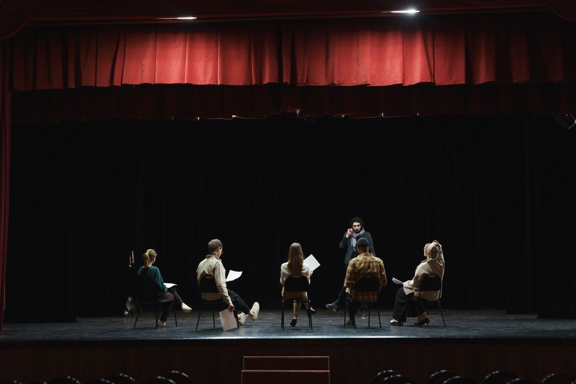 Actors reading a script on a theater stage