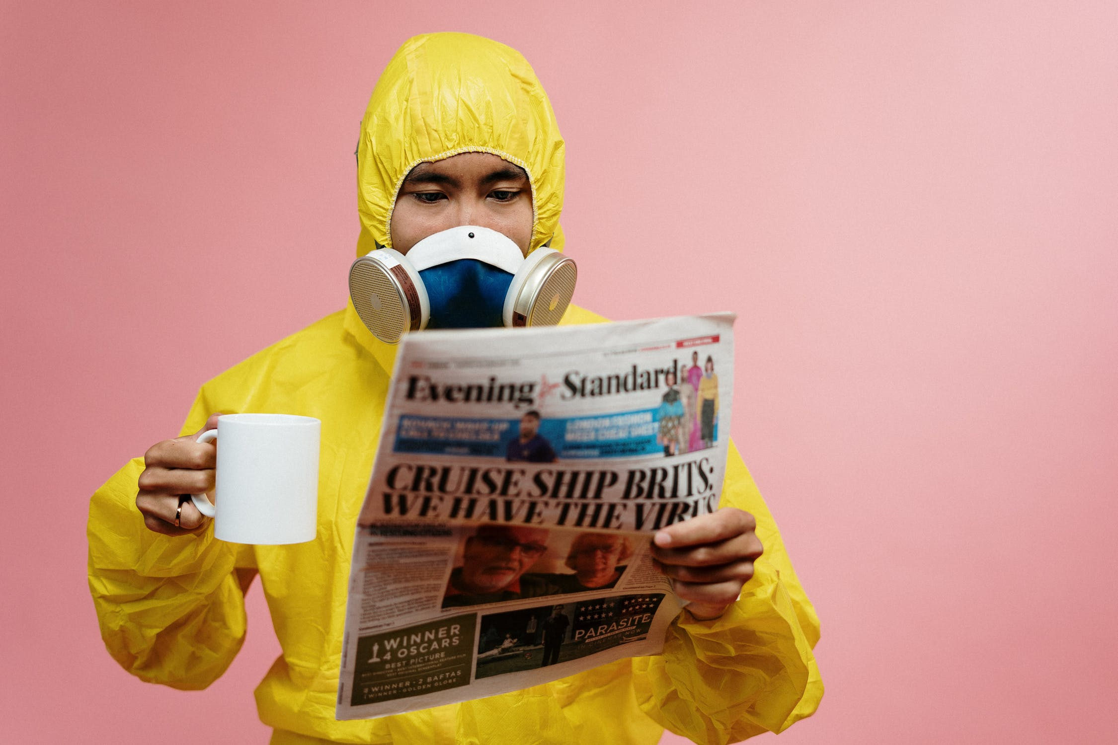 A man with a respirator, reading newspaper and drinking a cup of coffee