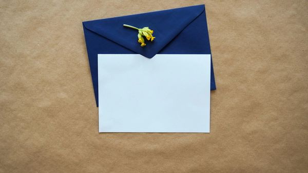 Blue letter envelope with a white paper on brown background.