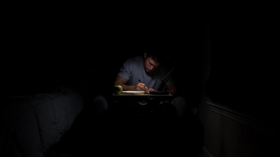 Jeune homme écrivant dans la nuit