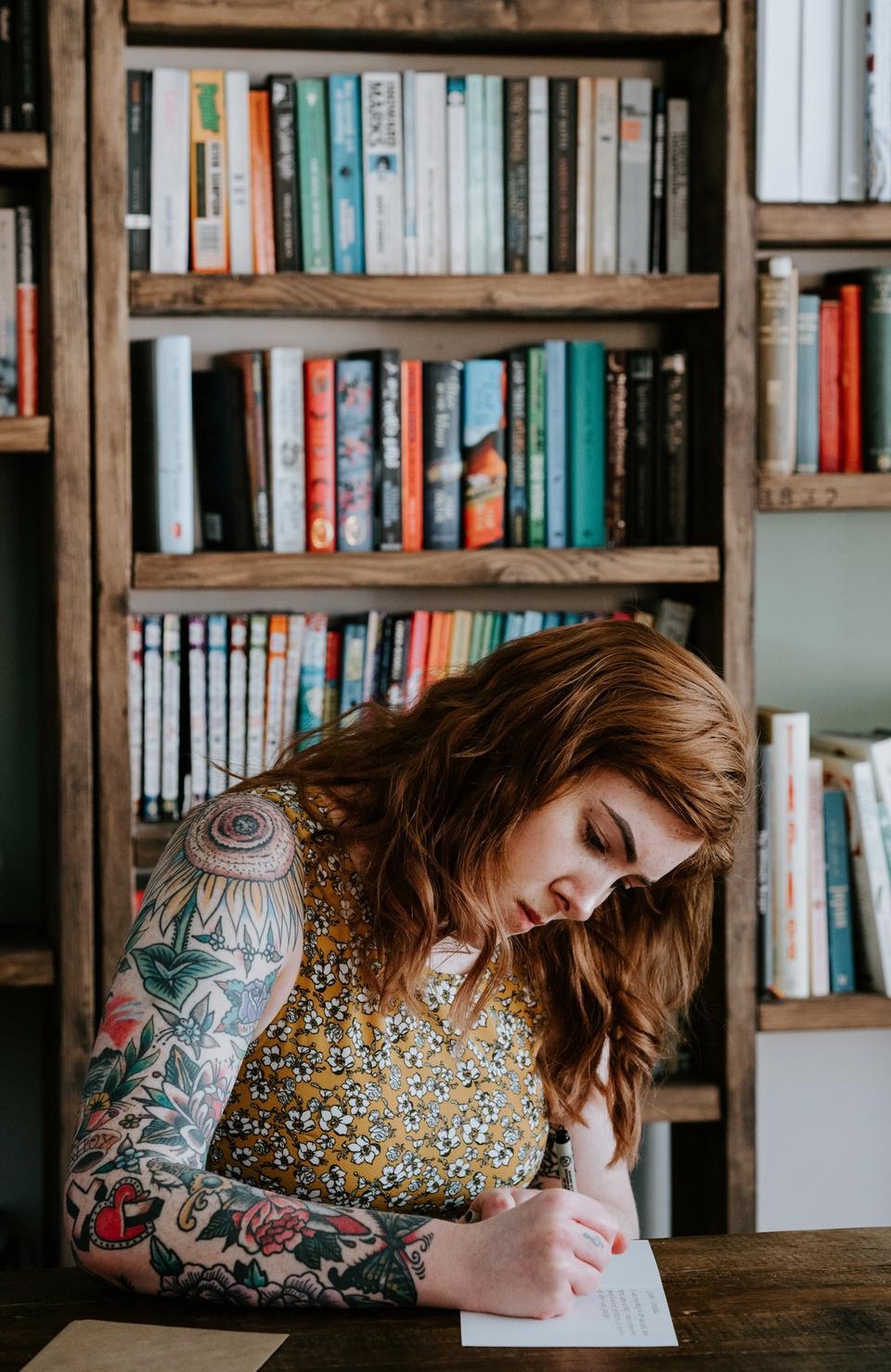 Jeune femme écrivant dans sa bibliothèque