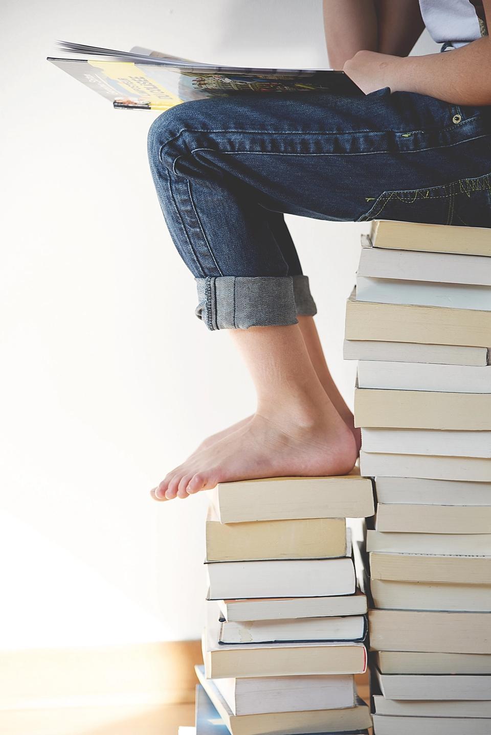 Jeune femme assise sur pile de livres