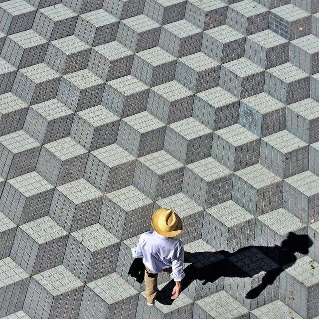 Homme marchant sur cubes en trompe-l'oeil