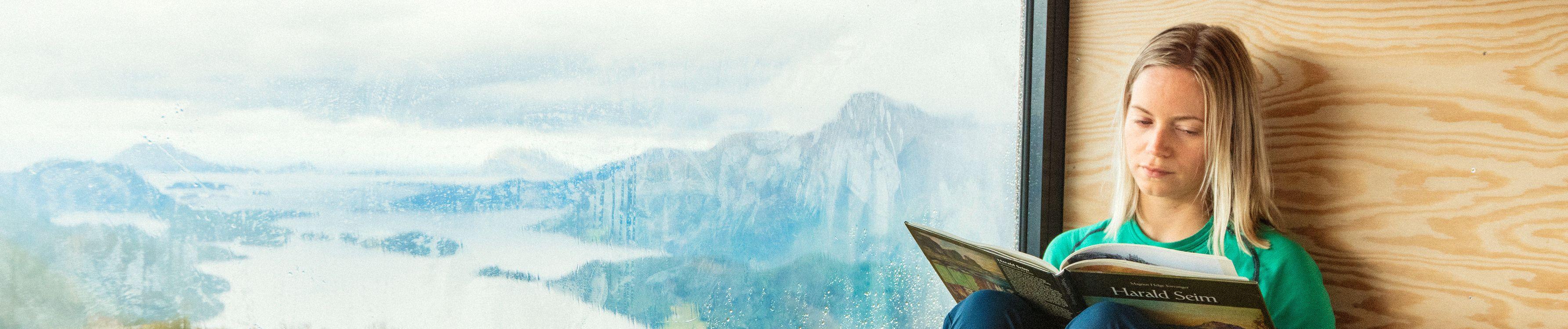 Illustrasjonsbilde: Kvinne sit i vinduskarmen og les