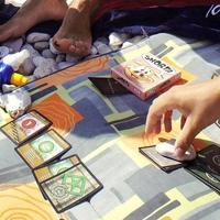 """Jeśli odważycie się zabrać planszowkę """"w teren"""", istnieje duża szansa, że będziecie musieli przygniatać karty kamieniem,..."""