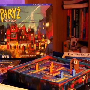 Zbliżenie na pudełko oraz inne elementy gry. (Paryż: Miasto Świateł)