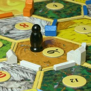 Złodziej stojący na planszy oraz budynki białego gracza (Catan)