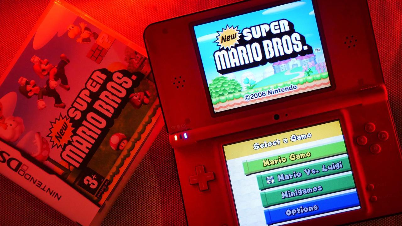 New Super Mario Bros., proj. Shigeyuki Asuke; po prawej: konsola Nintendo DSi XL z włączoną grą.