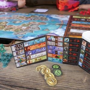 Elementy gry rozłożone na stole. Każdy z graczy posiada parawan, za którym ukrywa przed innymi ilość posiadanego złota, co może mieć znaczenie podczas licytacji. (Cyklady: Tytani)