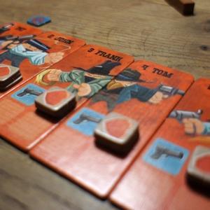 Planszetki bandytów i żetony oznaczające ich punkty życia. (Flick 'em Up!)