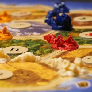 Zbliżenie na planszę do gry. Na planszy osady, drogi i miasta graczy oraz żetony z liczbami. (Catan)