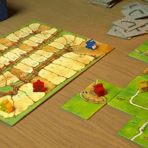 Po lewej plansza do podliczania punktów; po prawej plansza ułożona z kafelków w trakcie gry. (Carcassonne)