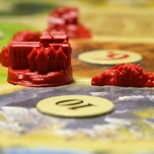 Zbliżenie na czerwone miasto i drogę (Catan)