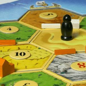 Złodziej stojący na planszy w starszym wydaniu gry (Catan)